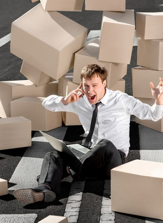 Crying and shocked businessman speaking phone and sitting with laptop on the asphalt road surrounded by falling carton boxes